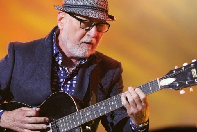 Image de Patrick Norman jouant de la guitare